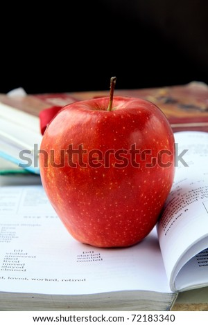 red ripe apple with English textbooks on a black background