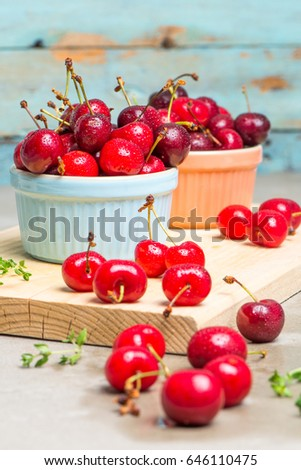 Red ripe cherries in ceramic bowls on kitchen countertop. #646110475
