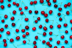 Red ripe cherry berries on blue background. Cherry pattern. Flat lay. Healthy food concept.
