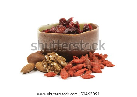 Red ripe dried cranberries in a small green and brown bowl with mixed nuts and goji berries on a reflective white background