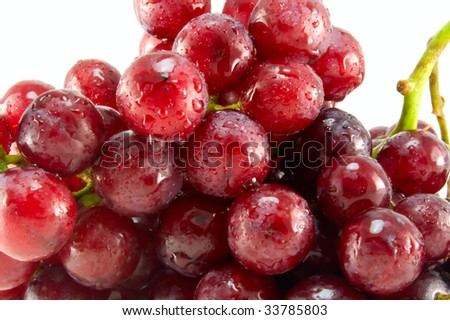 Red ripe grape with  drops of water. White background.