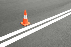 Red road cone on asphalt road with a newly painted white line. Road line and a cone.