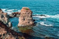 Red rock illuminated by the sun and blue sea.  Rocky Black Sea coast near the village of Rezovo, Bulgaria.