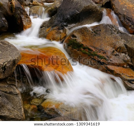 Red rock in waterfall rapids on Bridalveil Creek below the Fall in Yosemite Valley