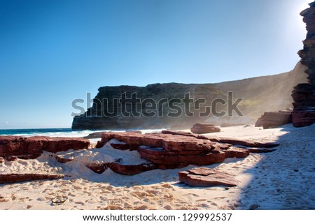 Red rock on misty beach. Shot in the Cape of Good Hope and Cape Point Nature Reserve, Table Mountain National Park, near Cape Town, South Africa. - stock photo