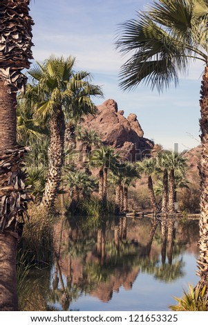 Red Rocks of sandstone with tropical lagoon in Papago Park, Phoenix, Arizona