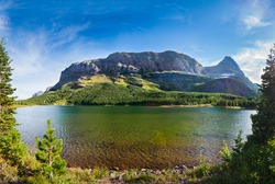 Red rocks, pine trees, and clear green water at Red Rock Lake in Glacier National Park, Montana