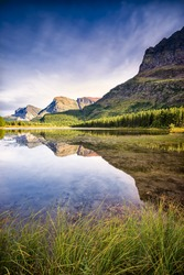 Red rocks, pine trees, and clear reflecting water at Red Rock Lake in Glacier National Park, Montana on a late summer afternoon