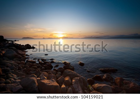 red rocky beach with clear water and islands on the horizon