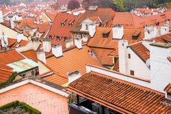 Red roof of buildings in Prague in a cold cloudy fall weather. Old town of Prague with tiled roofs. Red roofs. Europe.