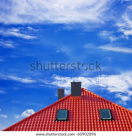 Red roof of new detached house against blue sky.