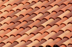 Red roof tiles or shingles on house as background image. Old and used overlapping red classic style roofing material texture pattern on a actual house.