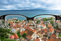 Red roofs and blue sea in Croatian city landscape focused in women's glasses frame. View through eyeglasses. Better vision concept.