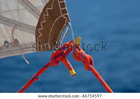 red rope, knot and piece of sail isolated on blue on sailing boat