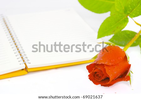 Red rose and orange notebook isolated
