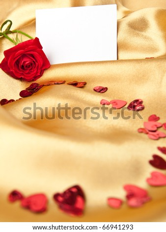 Red rose and white blank greeting card on golden satin