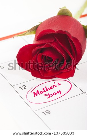 Red rose bud on calendar showing mothers day