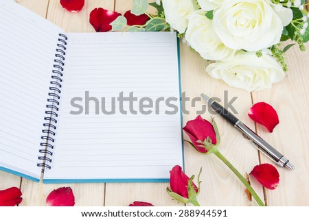 Red rose flower and Notepad book on wood texture.
