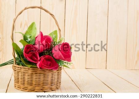 Red rose flower in vintage weave wicker basket on wood background.
