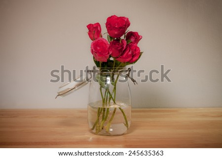 Red rose in glass canister on wooden desk top, romantic still life.