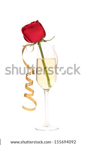 Red rose in glass of champagne and paper streamer. Isolated on white background.