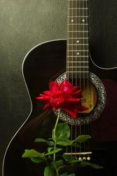 Red rose on a black acoustic guitar