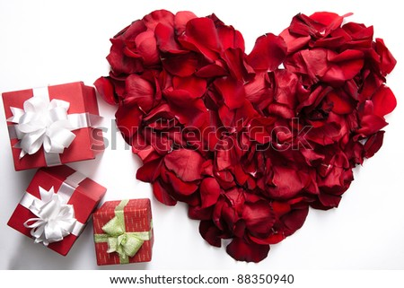 Red rose petals making up heart with small giftboxes near by