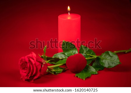 red rose, red candle and red heart on a red background in honor of Valentine's day, wedding day, anniversary