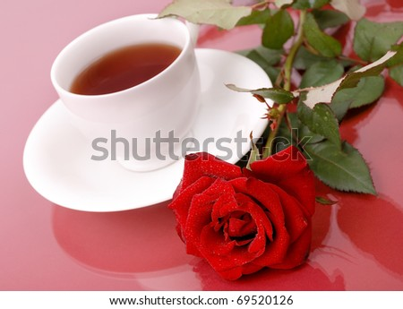 Red rose with cup of tea on red background. - stock photo