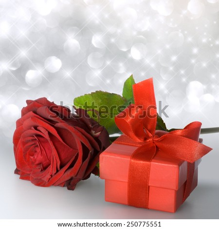 Red rose with red gift package on silver bachground