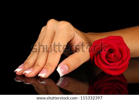 Red rose with woman's hand on black background