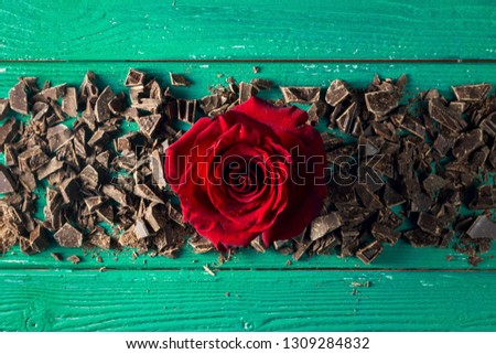 Red rosebud with chopped chocolate for St Valentine's day on a green wooden backdrop, top view #1309284832