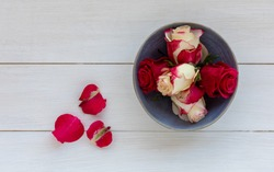 Red rosebuds in blue bowl on a white rustic background.