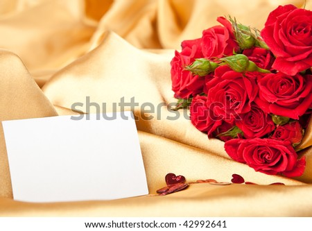 Red roses and blank invitation card on golden satin