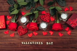 Red roses and candles on dark wooden background. Valentine's day, place for text.