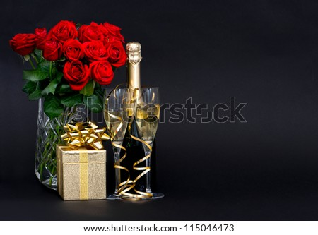red roses and champagne with golden decoration on black background. romantic arrangement. space for your text. selective focus