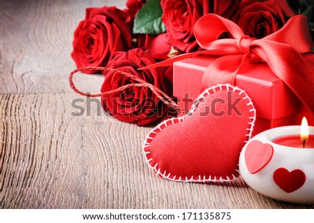 Red roses and gift box in St Valentine\'s setting