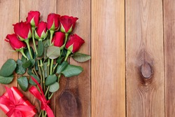 Red roses and gift box with ribbon, over wooden background flat lay. Valentine's Day, Birthday abstract background with copy space.