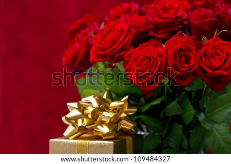 red roses and golden gift with ribbon. festive decoration. romantic arrangement