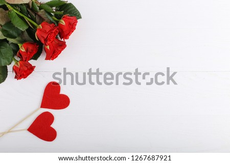 Red roses and hearts on white wooden table. Concept Women's Day or St. Valentine. Copy space. #1267687921