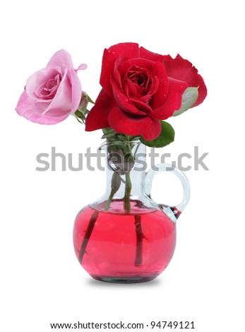 red roses and pink rose in glass vase isolated on white