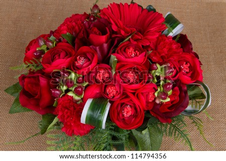 Red roses arranged in groups on sackcloth