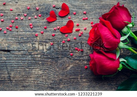 Red roses flowers with red hearts on old wooden background with place for text. Romantic Valentines holidays concept. Valentine's day greeting card. Copy space. Top view.