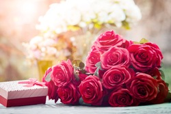 red roses flowers with valentine festival gift and beautiful blur bouquet background