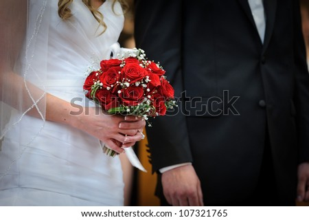 Red roses in brides hands
