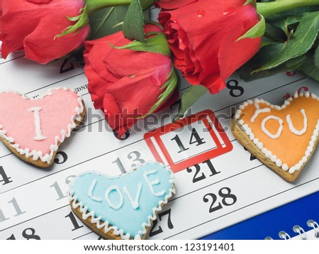 "red roses lay on the calendar with the date of February 14 Valentine's day and cookies with the words ""I love you"""