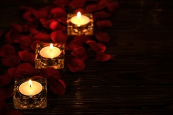 Red roses petals with butning candles on dark wooden background with copy space