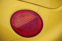 Red round brake light of a yellow car.