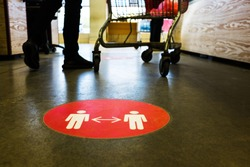 Red round circle sign printed on supermarket grocery store floor,ordering people to queue up at checkout keeping social distance,protection & prevention of spread & transfer of viruses,germs,bacteria