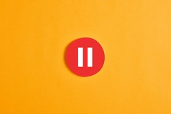 Red round circle with a pause button or icon against yellow background.